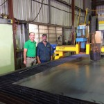General Manager Troy Law (left) and operator Graham Hunt in front of the ART HDP plasma cutter in their Dalby-based factory.